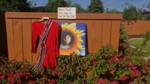 "Portrait of Ashlynne Mike next to ceremonial dress, and a handwritten sign that reads ""No one should have to look for their child."""