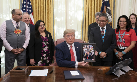 President Trump signs proclamation in the oval office with Native American representatives present